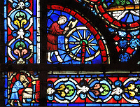 A wheelwright runs his adze over a cartwheel to check it, from the donor window of the woodworkers, from the Life of Noah stained glass window, 13th century, in the nave of Chartres cathedral, Eure-et-Loir, France. Chartres cathedral was built 1194-1250 and is a fine example of Gothic architecture. Most of its windows date from 1205-40 although a few earlier 12th century examples are also intact. It was declared a UNESCO World Heritage Site in 1979. Picture by Manuel Cohen