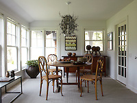 Bentwood chairs around an antique round table in a bright dining room