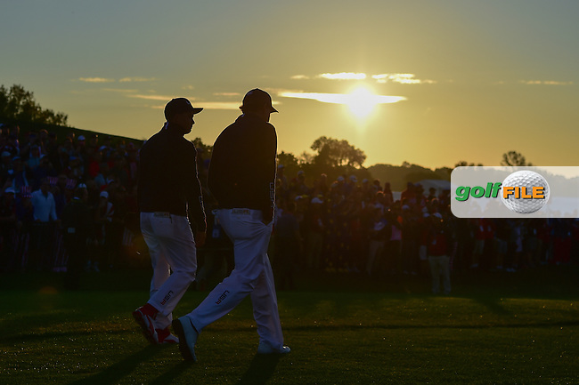 Phil Mickelson (USA) and Rickie Fowler (USA) depart the first tee as the sun rises during the Saturday morning foursomes at the Ryder Cup, Hazeltine National Golf Club, Chaska, Minnesota, USA.  10/1/2016<br /> Picture: Golffile | Ken Murray<br /> <br /> <br /> All photo usage must carry mandatory copyright credit (&copy; Golffile | Ken Murray)