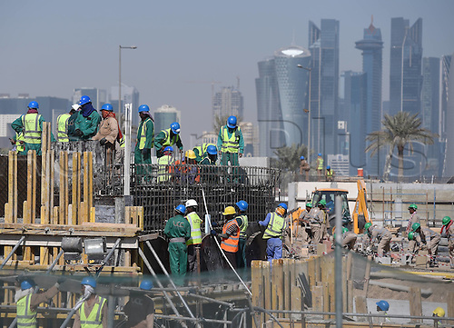 21.12.2014 Doha Qatar. FIFA World Cup 2022 in Qatar preparations show a bulding site and workers in front of the Skyline in Doha