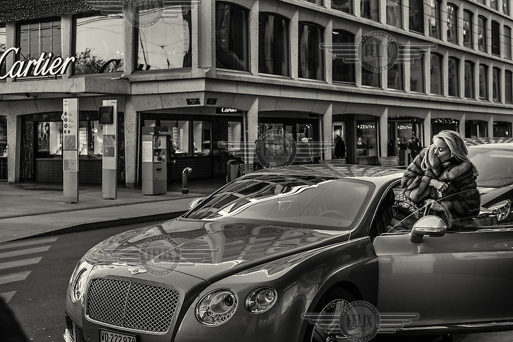 A woman, dressed in fur and clutching a Chanel purse, enters a Bentley car parked near a Cartier shop on Rue du Rhone, a thoroughfare reknown for its luxury brand shops.
