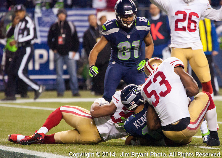 San Francisco 49er linebacker NaVorro Bowman (53) has his knee bent back after while stripping the ball away from Seattle Seahawks wide receiver Jermaine Kearse in their NFL  Championship Game against the Seattle Seahawks at CenturyLink Field in Seattle, Washington on January 19, 2014.  The Seahawks beat the 49ers 23-17 to represent the NFC in the Super Bowl.  ©2014. Jim Bryant Photo. ALL RIGHTS RESERVED.