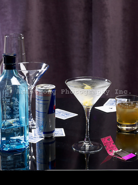 A martini on the bar. Pictured with bottle of gin, Red Bull can, whiskey cocktail, playing cards, matchbook, and empty glassware.