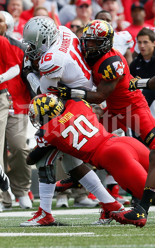Ohio State Buckeyes quarterback J.T. Barrett (16) is tackled by Maryland Terrapins defensive back Anthony Nixon (20) in the first quarter of their game at Byrd Stadium in College Park, Maryland on October 4, 2014. (Columbus Dispatch photo by Brooke LaValley)
