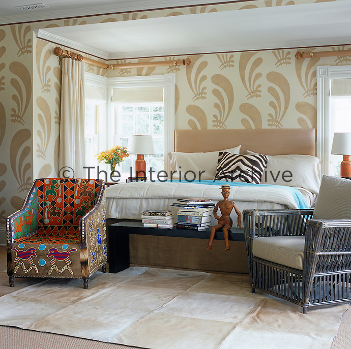 The walls of the bedroom are stencilled with a bold pattern in neutral colours