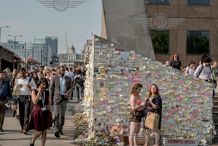 Commuters walk past an informal memorial, at the approach to London Bridge, made up of flowers and notes to the victims of the 3 June 2017 terrorist attack.