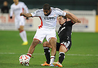 Washington, D.C.- March 29, 2014. Andrew Farrell (2) of the New England Revolution goes against Lewis Neal (24) of D.C. United. D.C. United defeated the New England Revolution 2-0 during a Major League Soccer Match for the 2014 season at RFK Stadium.