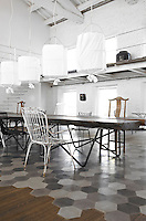 The dining area is furnished with a collection of mismatched chairs grouped around a table made of Swamp Kauri, a prehistoric wood and the cylindrical lamps are by  Mark Eden Schooley