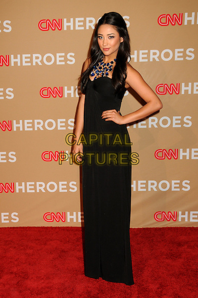SHAY MITCHELL .CNN Heroes: An All-Star Tribute 2010 held at the Shrine Auditorium, Los Angeles, California, USA, .20th November 2010..full length black dress long maxi hand on hip strapless blue stone necklace .CAP/ADM/BP.©Byron Purvis/AdMedia/Capital Pictures.