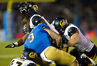 Damariay Drew of California loses his helmet while tackles Darius Bell of UCLA during the game at Rose Bowl in Pasadena, California on October 12th, 2013.   UCLA defeated California, 37-10.