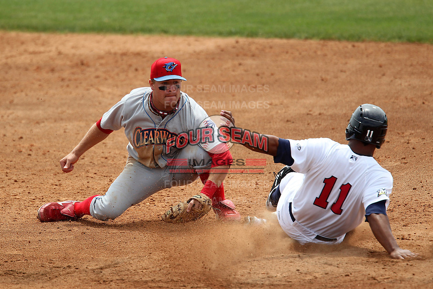 Clearwater Threshers shortstop Carlos Alonso #17 attempts to tag out Miguel Velazquez #11 during a game against the Brevard County Manatees at Space Coast Stadium on April 30, 2012 in Viera, Florida.  Clearwater defeated Brevard County 5-1.  (Mike Janes/Four Seam Images)