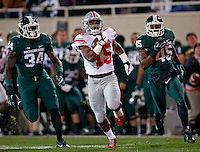 Ohio State Buckeyes running back Ezekiel Elliott (15) gets past Michigan State Spartans linebacker Taiwan Jones (34) and Michigan State Spartans linebacker Darien Harris (45) on a rush during the 1st quarter at Spartan Stadium in East Lansing, Michigan on November 8, 2014.  (Dispatch photo by Kyle Robertson)