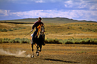 Cowboy riding horse on the dusty prairie of Billings Montana