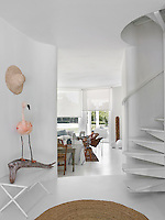 A spiral staircase, echoing the shape of the  circular entrance hall, leads off to the upstairs rooms