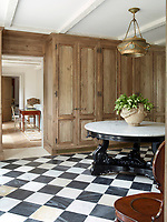 The front hall's Indian table and English chandelier and chair are 19th-century and the the black and white check pattern marble flooring is by Exquisite Surfaces. Built-in wood cupboards provide plenty of storage space.