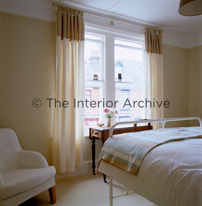 The simple bedroom has a neutral colour palette and a wrought-iron bed