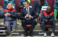 (L-R) Swansea City Assistant manager, Nigel Gibbs, Swansea manager Paul Clement and Swansea assistant coach Claude Makelele sit on the bench during the Premier League match between West Ham United v Swansea City at the London Stadium, London, England, UK. Saturday 30 September 2017