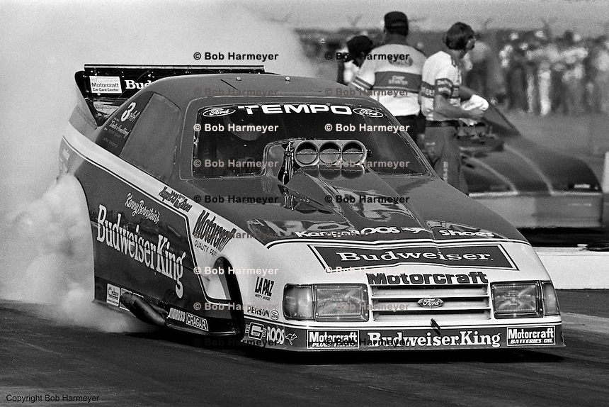 "POMONA, CALIFORNIA: Kenny Bernstein drives his ""Budweiser King"" Ford Funny Car during a 1985 NHRA drag race at Pomona, California."