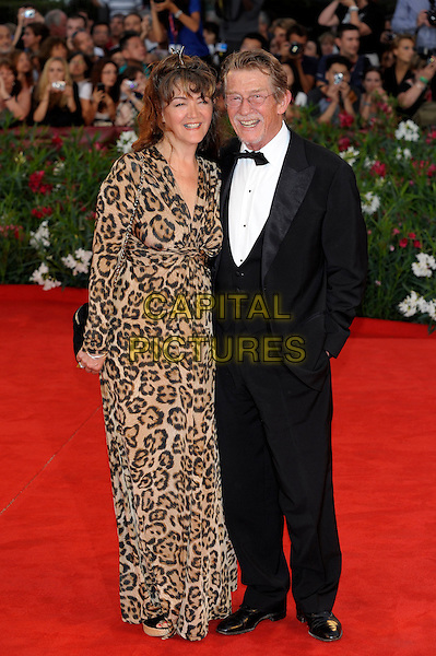 Anwen Rees Meyers &amp; John Hurt<br /> The 'Tinker, Tailor, Soldier, Spy' premiere at the Palazzo del Cinema during the 68th Venice Film Festival, Venice, Italy.<br /> September 5th, 2011<br /> full length black tuxedo leopard print brown dress married husband wife <br /> CAP/PL<br /> &copy;Phil Loftus/Capital Pictures