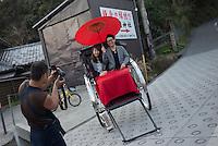Rickshaw driver taking photos of tourists on rickshaw Enoshima, Kanagawa, Japan