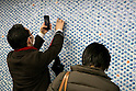 "Pedestrians interact with a wall of 100,000 Slime characters in Shinjuku Station on February 26, 2015. 100,000 Blue Slime from the game of Dragon Quest are displayed in bubble-wrap in a corridor of Shinjuku Station. The wall was created to promote the newest video game ""Dragon Quest Heroes: The Dark Dragon and the World Tree Castle"" for Playstation 3 and 4. Passersby can pop the Slimes and the goal of for all 100,000 bubbles to have been burst by the end of the campaign. There are special characters such as metal Slimes and Rockbombs hidden along the wall and the installation is accompanied by background music from the game. The promotion runs from February 23rd to March 1st in Tokyo. (Photo by Rodrigo Reyes Marin/AFLO)"