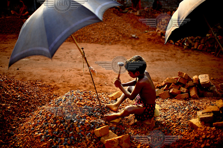 A young boy, protected from the sun by an umbrella, crushes bricks into chippings at a brick making factory.