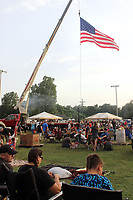 MEGAN DAVIS MCDONALD COUNTY PRESS/The American flag, suspended from a fire engine, flitters above patriotic people, enjoying watermelon, music, family and friends during the 2018 Third of July Celebration.