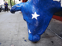 USA. New York City. A blue american cow sculpture outside a restaurant. A tourist takes a picture with a small digital camera. 25.10.2011 © 2011 Didier Ruef