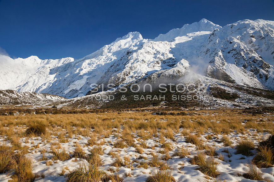 Snow & native grasses with Sefton Range. Hooker Valley track Aoraki Mt Cook National Park NZ.