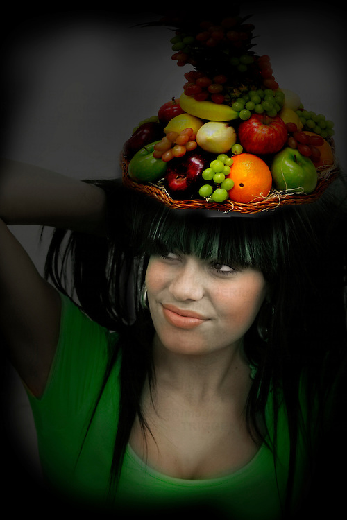 colourful young woman with a basket of fruit n her head