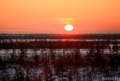 The sun sets over the ice tundra as seen from the Achimgaz drilling well in Novy Urengoi, Siberia, Russia.