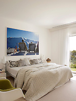 A modern bedroom decorated in neutral tones. A large photograph by Philipp Hofmann above the double bed provides a vibrant spot of colour.