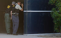 Phoenix, Arizona, USA-- Maricopa County Sheriff deputies look through a window while investigating Laser Masters in Phoenix. Deputies took 24 people into custody during an identity theft investigation. Most of the people arrested were thought to have used false ID to get employment. (Pat Shannahan/ The Arizona Republic)