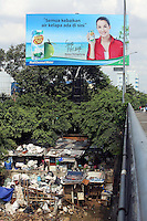A large advertisement hangs above a slum community in central Jakarta.<br />