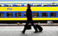Vrouw loopt op het perron in Venlo langs een dubbeldekker