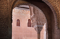 Small horseshoe arch in carved stucco in the portico of the the Patio of the Gilded Room, between the Mexuar and the Gilded Room or Cuarto Dorado in the Comares Palace, with intricately carved wall with latticed windows beyond, and a 12th century marble capital supporting another arch, Alhambra Palace, Granada, Andalusia, Southern Spain. It was built under Mohammed V in the 14th century. The Alhambra was begun in the 11th century as a castle, and in the 13th and 14th centuries served as the royal palace of the Nasrid sultans. The huge complex contains the Alcazaba, Nazrid palaces, gardens and Generalife. Picture by Manuel Cohen