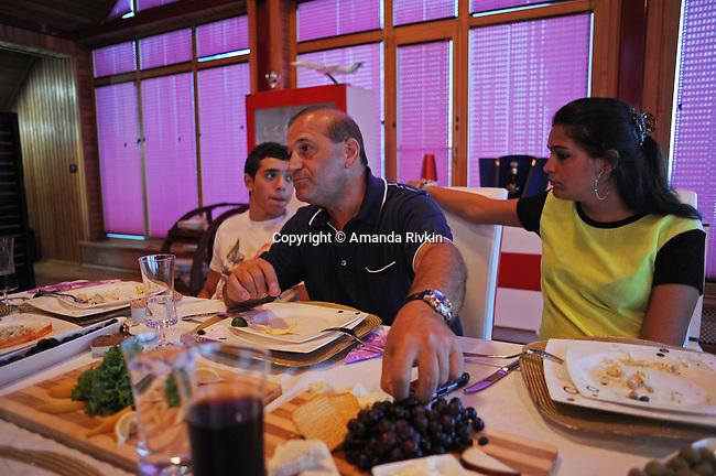 Ibrahim Ibrahimov (center) sits at the dinner table with his son Huseyn Ibrahimov, 18, and daughter Ilkana Ibrahimova, 22, in his home between Sangachal and Sahil, Azerbaijan on August 16, 2012.
