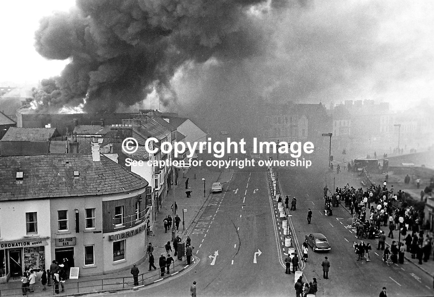 Bangor, Co Down, N Ireland, ablaze after 15 Provisional IRA bombs devastated the town centre. Traders and shoppers wait and watch on the fringes of the central shopping area. 197404040215b, 215/74<br />