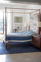 A full-height headboard in an Italian chinoiserie fabric was made  for the Duff Tisdall four-poster by Peter Johnson Interiors. The abstract painting is by Natasha Johnson's mother, Camille Souter. The chest of drawers on the right of the bed is Danish, made in the 1920's, and now reprouced ny Peter Johnson Interiors. The blue wool carpet is by McMurray Carpets, Connemara.