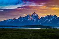 An amazing sunset lights up the Teton Range as it rises above Jackson Lake, Grand Teton National Park, Wyoming.