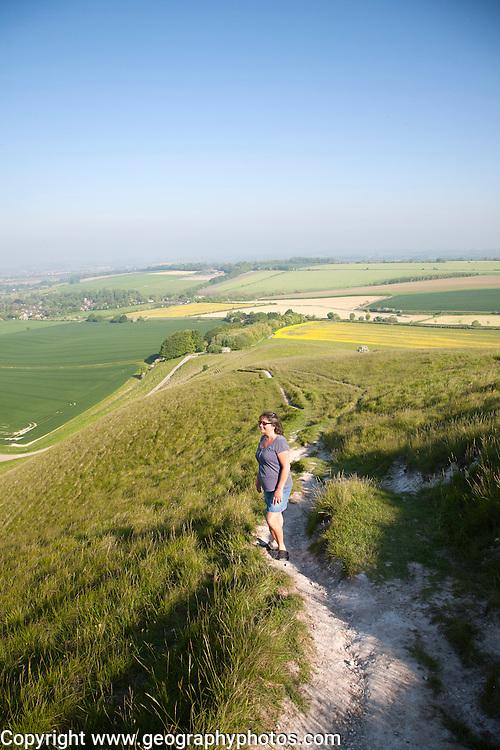 Woman walking up steep chalk scarp slope onto downland Cherhill, Wiltshire, England, UK