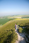 Woman walking up steep chalk scarp slope onto downland Cherhill, Wiltshire, England, UK