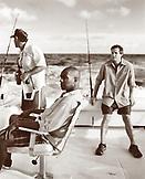 USA, Florida, three men waiting for fish to hit the line, Islamorada (B&W)