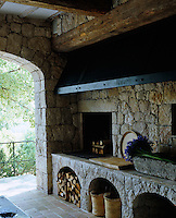 This rustic outdoor kitchen features a stove which also functions as a barbeque and a source of heat on cooler evenings