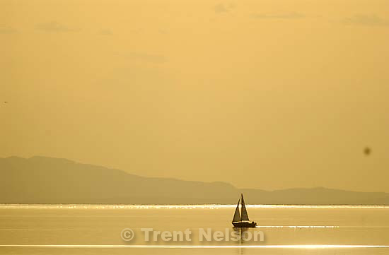At sunset, a pair of sailboats pass each other on the waters of the Great Salt Lake Tuesday evening.<br />