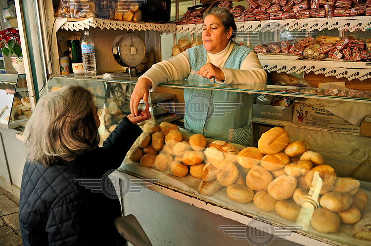A woman sells bread in a city market.