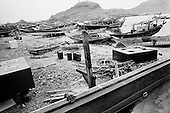 Sur, Oman<br /> July 2001<br /> <br /> Dhow builders use ropes, wood beams and nails to climb into place.
