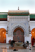 Low angle view of men washing their feet in the courtyard, Mosque and University of Al-Karaouine, founded 859, Fez, Morocco, pictured on February 22, 2009 in the evening. The University of Al-Karaouine was an important Medieval centre for cultural and academic exchange between the Islamic states and Europe having, nurtured many influential scholars of the Muslim and Jewish worlds. Its Madrasa is still a great Islamic spiritual and educational centre. Fez, Morocco's second largest city, and one of the four imperial cities, was founded in 789 by Idris I on the banks of the River Fez. The oldest university in the world is here and the city is still the Moroccan cultural and spiritual centre. Fez has three sectors: the oldest part, the walled city of Fes-el-Bali, houses Morocco's largest medina and is a UNESCO World Heritage Site;  Fes-el-Jedid was founded in 1244 as a new capital by the Merenid dynasty, and contains the Mellah, or Jewish quarter; Ville Nouvelle was built by the French who took over most of Morocco in 1912 and transferred the capital to Rabat. Picture by Manuel Cohen.