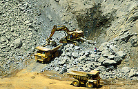 Tracked loader and heavy duty dump trucks working in gold mine in southern Africa..