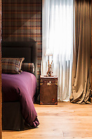 Each of the bedrooms has a different colour scheme with walls covered in a warm-toned plaid